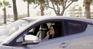 Tel?fono que habla sonriente del modelo en coche almacen de metraje de vídeo