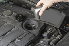 Tel olie aan motor van een auto van fles op royalty-vrije stock foto