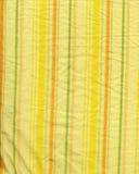 Tela amarilla de la raya con las arrugas Fotografía de archivo