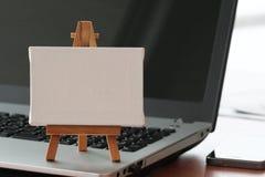 Tela in bianco e cavalletto di legno sul computer portatile Immagini Stock