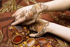 Tela brillante anaranjada de la imagen del mehendi de las manos de dos mujeres con los plisados Imagenes de archivo