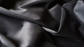 A tela composta de seda preta de pano curva o fundo da textura Fotografia de Stock Royalty Free