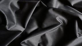 A tela composta de seda preta de pano curva o fundo da textura Fotos de Stock Royalty Free