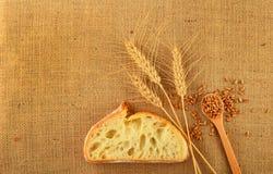 Tela con le orecchie del grano, il pane ed i grani maturi Fotografia Stock