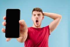 Tela considerável nova do smartphone da exibição do homem isolada no fundo azul em choque com uma cara da surpresa fotos de stock