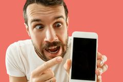 Tela considerável nova do smartphone da exibição do homem isolada no fundo coral em choque com uma cara da surpresa fotografia de stock