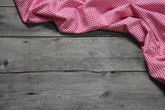 Tela a cuadros como frontera en fondo de madera gris Imagen de archivo libre de regalías