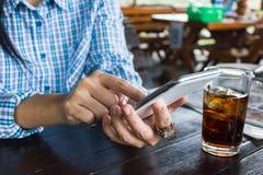 Tela da imprensa da mão das mulheres ou smartphone móvel, vidro do refresco com gelo na tabela de madeira Imagens de Stock Royalty Free