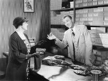 Tela de compra de la mujer de un vendedor de las ventas en grandes almacenes (todas las personas representadas no son vivas más l imagen de archivo libre de regalías
