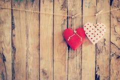 Tela de dois corações que pendura no fundo da corda e da madeira com Foto de Stock