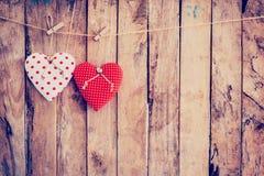 Tela de dois corações que pendura no fundo da corda e da madeira com Foto de Stock Royalty Free