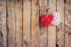 Tela de dois corações que pendura no fundo da corda e da madeira com Fotos de Stock