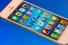 A tela de IPhone 5 Apps em um azul iluminou a superfície Fotografia de Stock