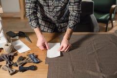 Tela de las lanas del corte la línea modelo Corbatas de lazo de la tela de lana Funcionamiento del hombre joven como sastre y usa Imagen de archivo