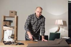 Tela de las lanas del corte la línea modelo Corbatas de lazo de la tela de lana Funcionamiento del hombre joven como sastre y usa Foto de archivo