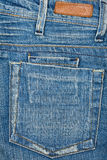 Tela de los tejanos con el bolsillo y la escritura de la etiqueta Fotos de archivo