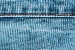 Tela de los tejanos con una textura del fondo de la costura Fotos de archivo