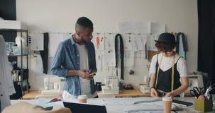 Tela de medición de la modista de sexo femenino mientras que hombre afroamericano usando smartphone almacen de video