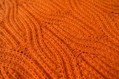 Tela de punto hecha a mano anaranjada brillante con el modelo de la trenza Fotos de archivo libres de regalías