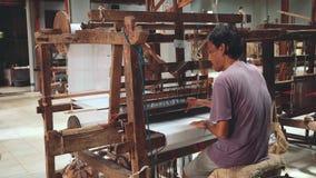 Tela de tecelagem indonésia do homem com a máquina do tear do pé-pedal video estoque