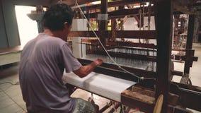Tela de tecelagem indonésia do homem com a máquina do tear do pé-pedal vídeos de arquivo