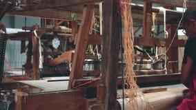 Tela de tecelagem indonésia dos homens com a máquina do tear do pé-pedal video estoque