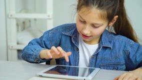 Tela de toque feliz da menina da tabuleta ao jogar jogos em linha video estoque