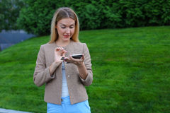 Tela de vista fêmea bonita do smartphone e sorrisos, suportes Foto de Stock