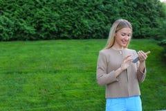 Tela de vista fêmea bonita do smartphone e sorrisos, suportes Fotos de Stock