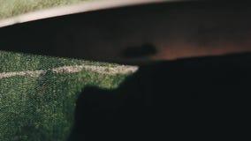 Tela del corte del sastre usando las tijeras o los esquileos grandes como él sigue las marcas de la tiza del modelo, cierre para  almacen de metraje de vídeo