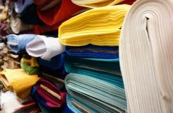 A tela e a matéria têxtil rolam no armazém Fotos de Stock