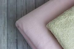 Tela escocesa rosada y toalla apiladas en un fondo de madera Fotos de archivo libres de regalías