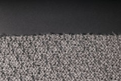 Tela gris hecha a mano en un fondo oscuro Foto de archivo