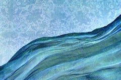 Tela iridiscente al lado del papel pintado del damasco Imagen de archivo libre de regalías