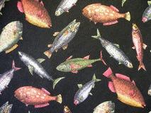 Tela negra con los pescados pintados foto de archivo