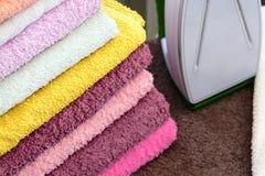 Tela rivestente di ferro con ferro Una pila di asciugamani rivestiti di ferro che si trovano accanto al ferro Ferro caldo su una  Fotografia Stock