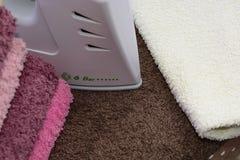 Tela rivestente di ferro con ferro Una pila di asciugamani rivestiti di ferro che si trovano accanto al ferro Ferro caldo su una  Immagine Stock