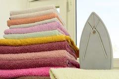 Tela rivestente di ferro con il generatore di vapore Una pila di asciugamani rivestiti di ferro che si trovano accanto al ferro S Immagini Stock