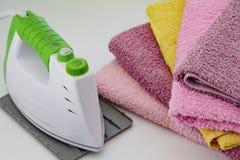 Tela rivestente di ferro con il generatore di vapore Una pila di asciugamani rivestiti di ferro che si trovano accanto al ferro S Fotografia Stock
