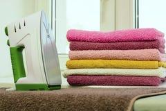 Tela rivestente di ferro con il generatore di vapore Una pila di asciugamani rivestiti di ferro che si trovano accanto al ferro S Fotografia Stock Libera da Diritti