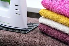 Tela rivestente di ferro con il generatore di vapore Una pila di asciugamani rivestiti di ferro che si trovano accanto al ferro S Immagine Stock Libera da Diritti