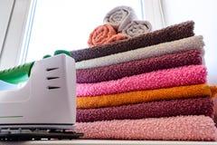 Tela rivestente di ferro con il generatore di vapore Una pila di asciugamani rivestiti di ferro che si trovano accanto al ferro S Fotografie Stock