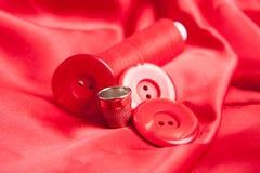 Tela roja y accesorios de costura Fotografía de archivo