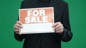 Tela superior do verde do homem de negócio com para sinal da venda video estoque