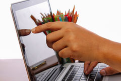 Tela táctil da mão e do dedo no monitor um portátil em uma tabela de madeira Foto de Stock
