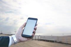 Tela táctil de um telefone celular, na mão de um homem de negócios na perspectiva do mar e do cais Foto para a zombaria acima Imagem de Stock Royalty Free