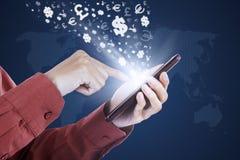Tela tocante do smartphone da mão com símbolos de moeda Imagens de Stock Royalty Free