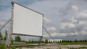 Tela vazia do cinema aberto do carro - tempo-lapso do quadro de avisos na frente das nuvens no dia ensolarado filme