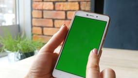 Tela verde Smartphone A chave do croma em um smartphone branco, as mãos fêmeas guarda o telefone celular em um café video estoque
