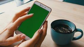 Tela verde Smartphone A chave do croma em um smartphone branco, as mãos fêmeas guarda o telefone celular em um café ao lado de um filme